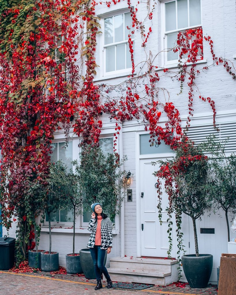 girl standing in kynance mews next to a house with red leaves