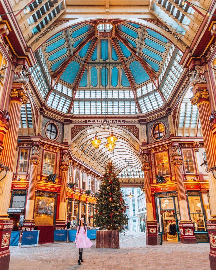 girl standing inside leadenhall market in london during christmas