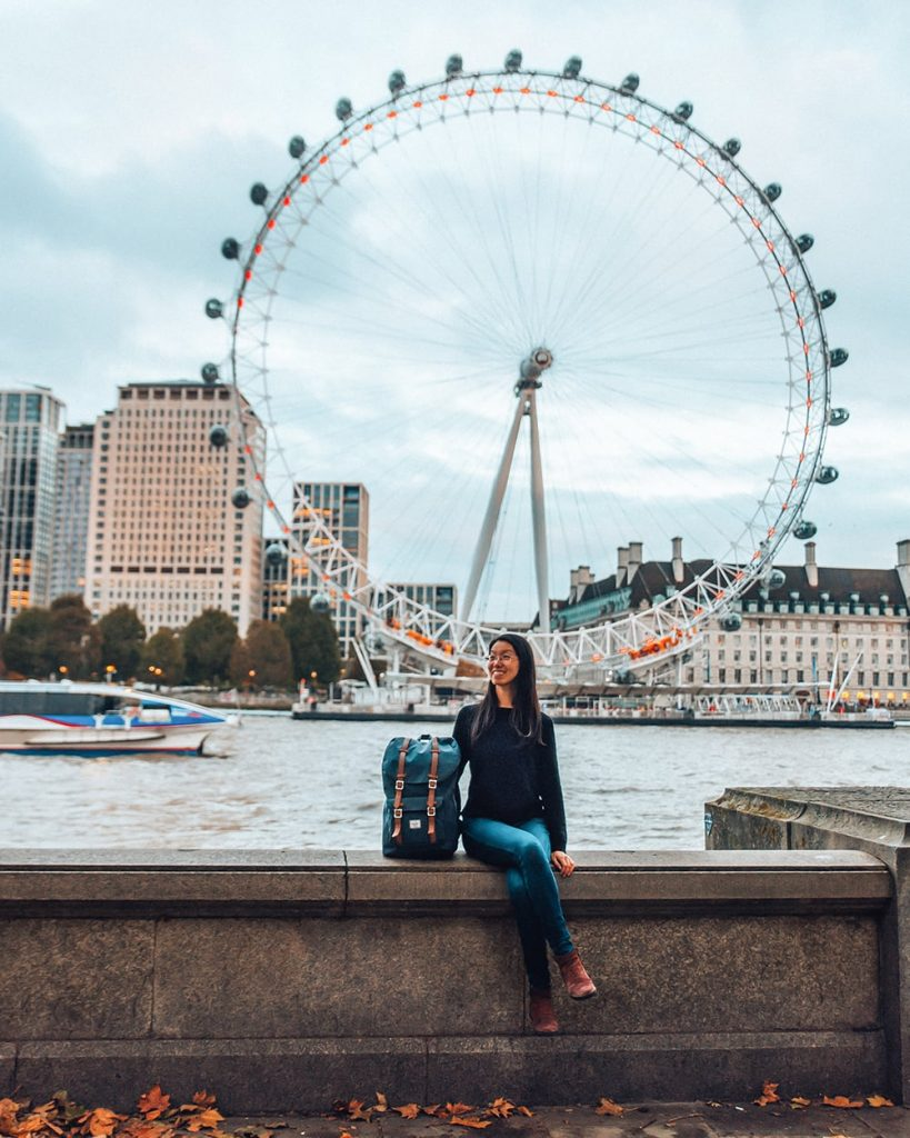 girl sitting in front of the london eye in the uk