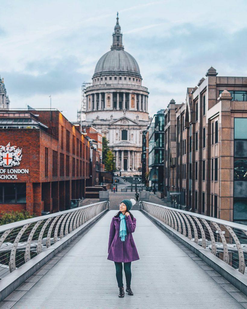 girl standing in the middle of millenium bridge in london