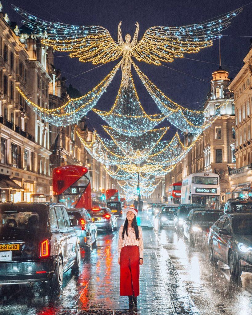 girl standing under christmas decorations in regent street in the uk