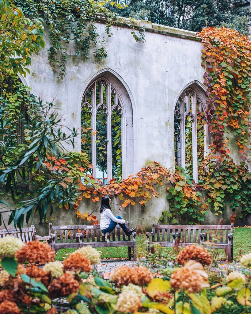 girl sitting in st dunstan in the east gardens in london with fall leaves around her