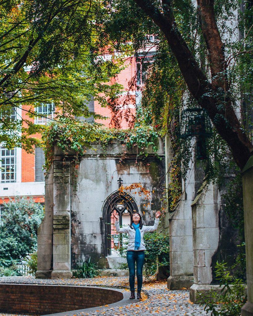 girl throwing leaves in st dunstan in the east gardens in london