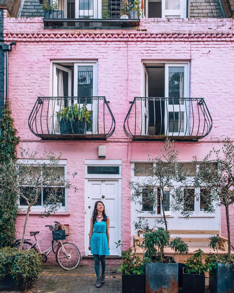girl standing in front of pink house in notting hill
