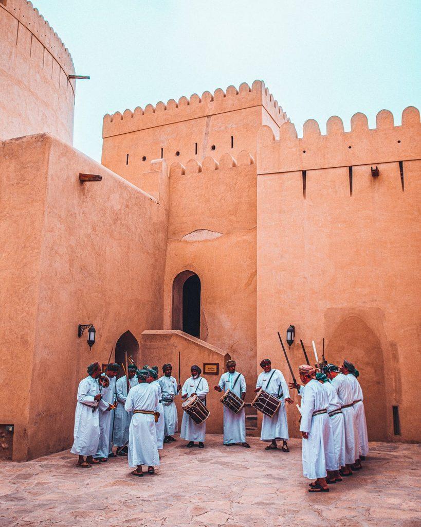 men performing traditional dance at nizwa fort