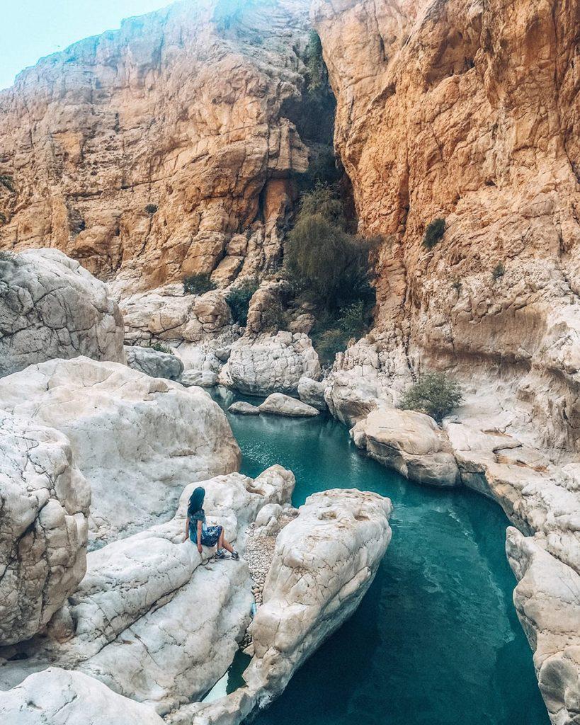 girl sitting on rock in wadi bani khalid in oman