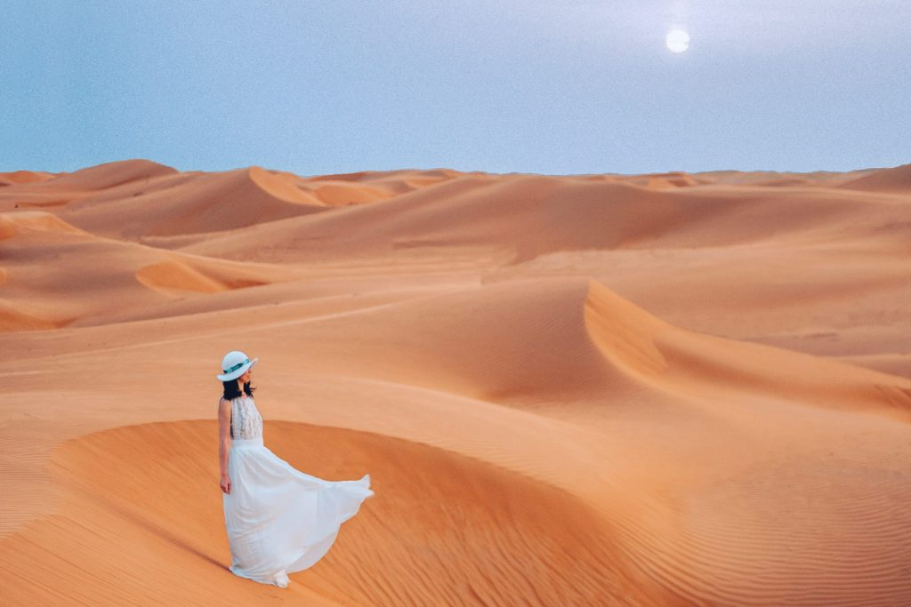 woman wearing a flowy dress standing on wahiba sands desert during her oman itinerary