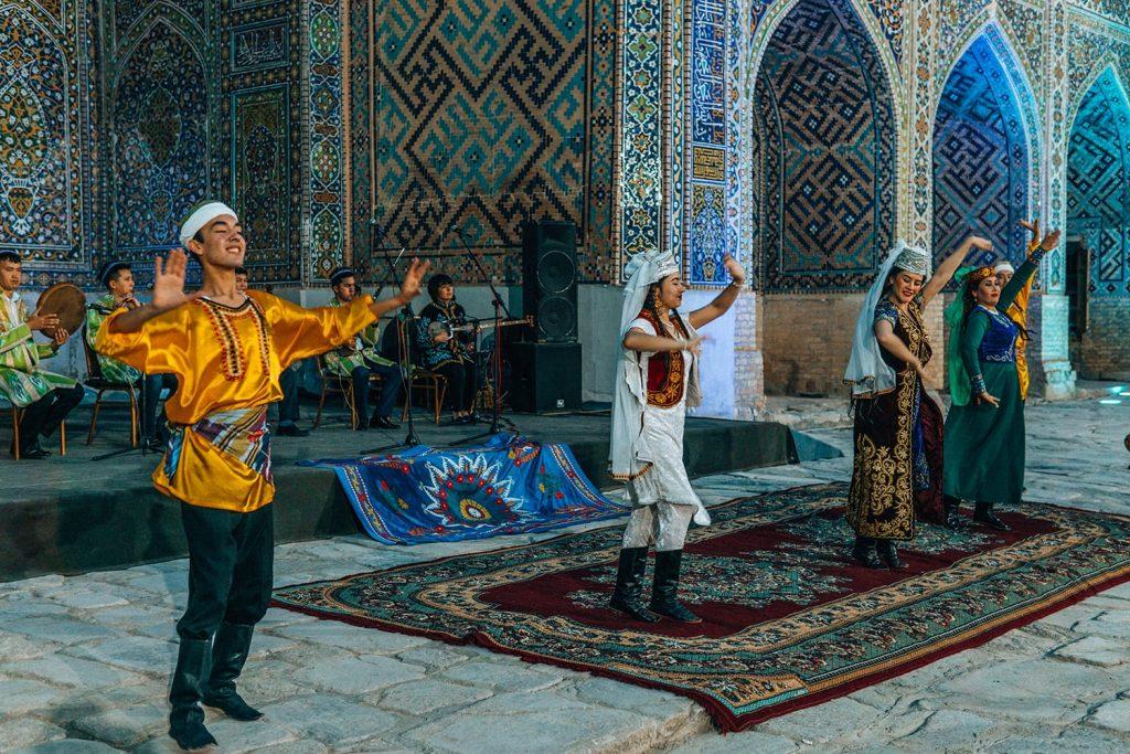 dancers performing in concert in front of madrasah tile work in registan square uzbekistan at night