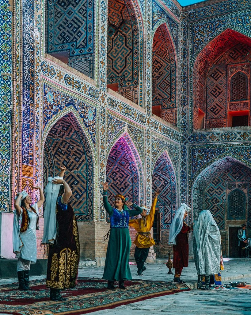 dancers performing in concert in front of madrasah tile work in registan square at night in samarkand