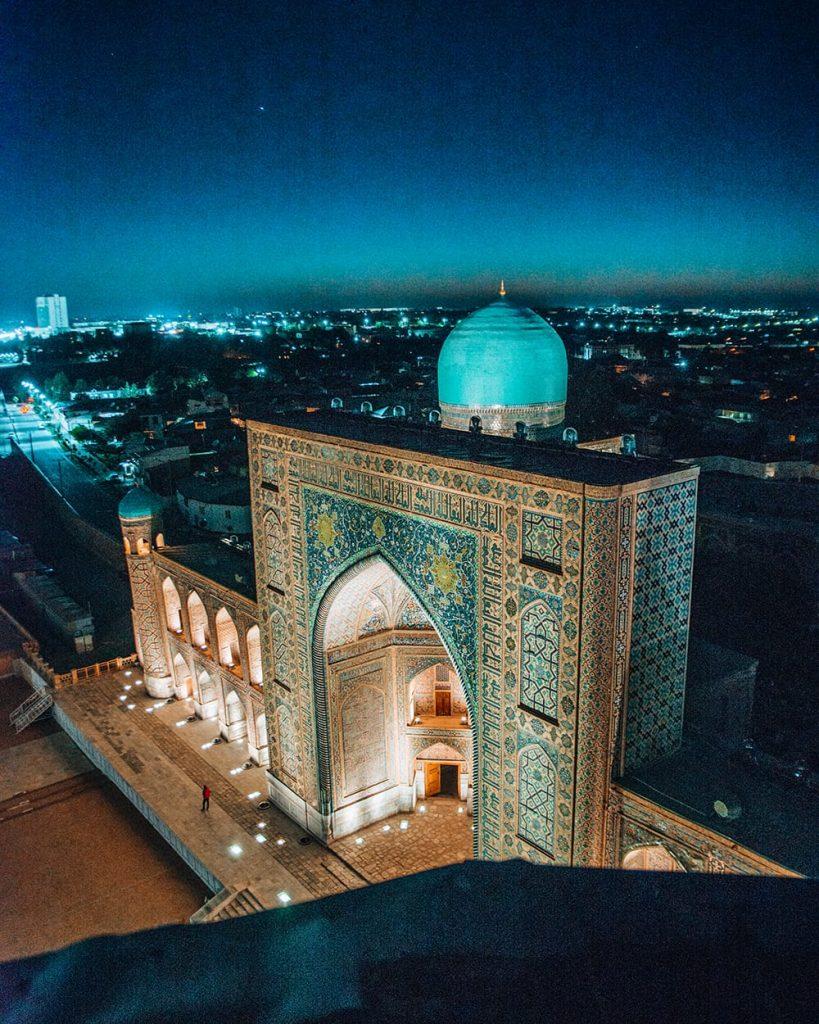 uzbekistan view of madrasah in registan square lit up at night from minaret