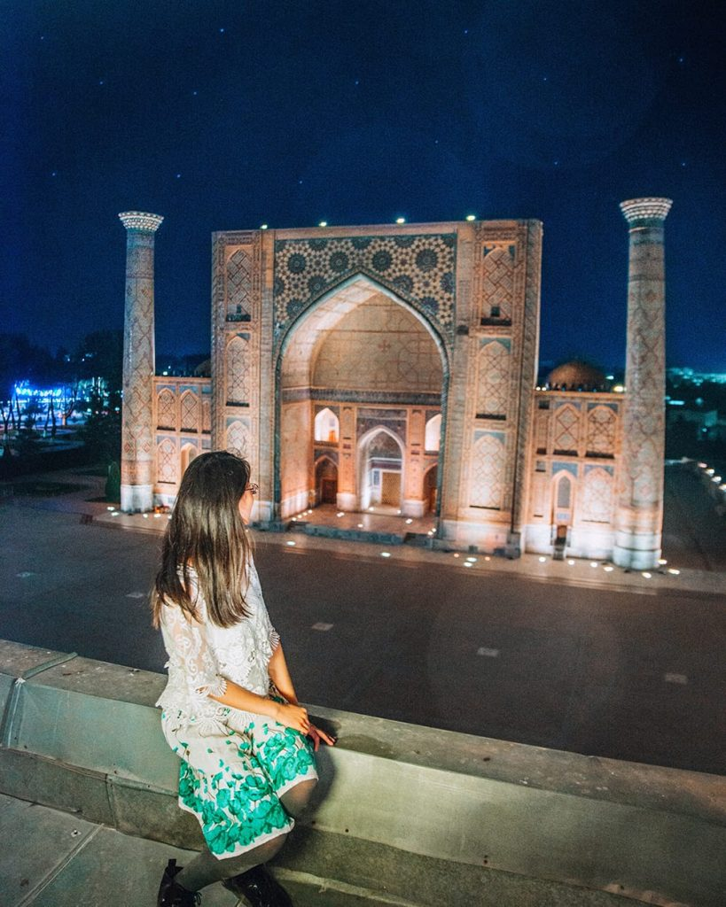 uzbekistan girl sitting on top of madrasah view of  registan square lit up at night