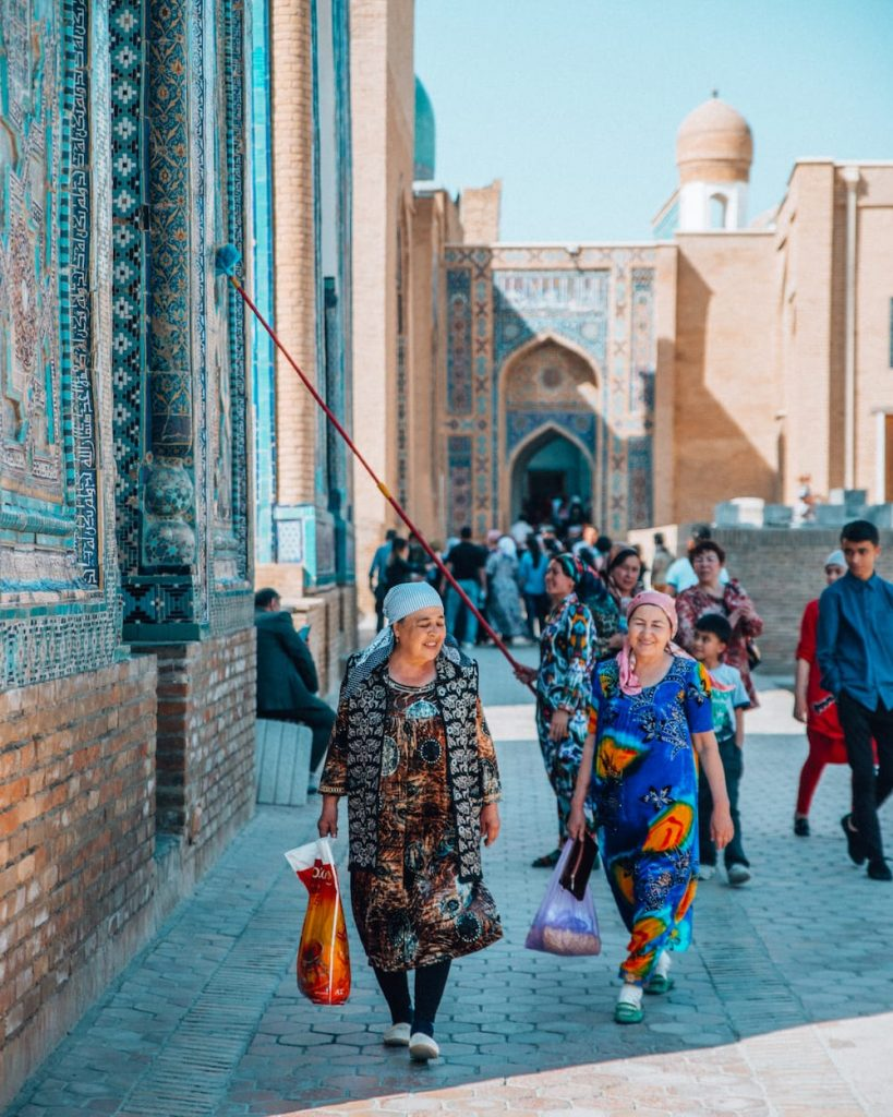 ladies in colorful clothing walking in shah i zinda mausoleum in uzbekistan