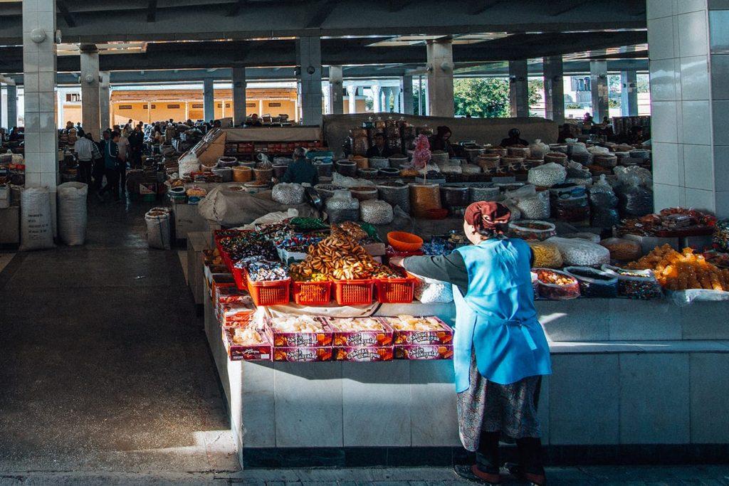 local uzbek lady standing next to spices in bazaar uzbekistan