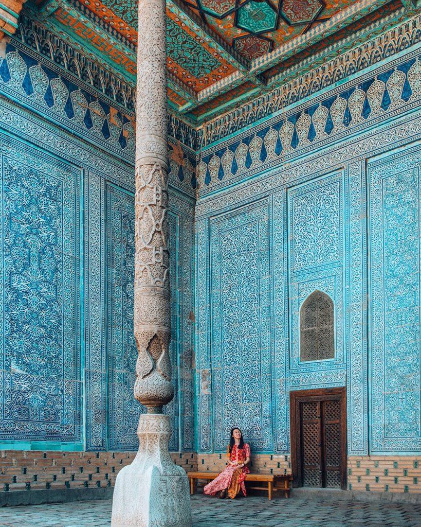 girl sitting inside tash hauli palace next to tilework in khiva uzbekistan