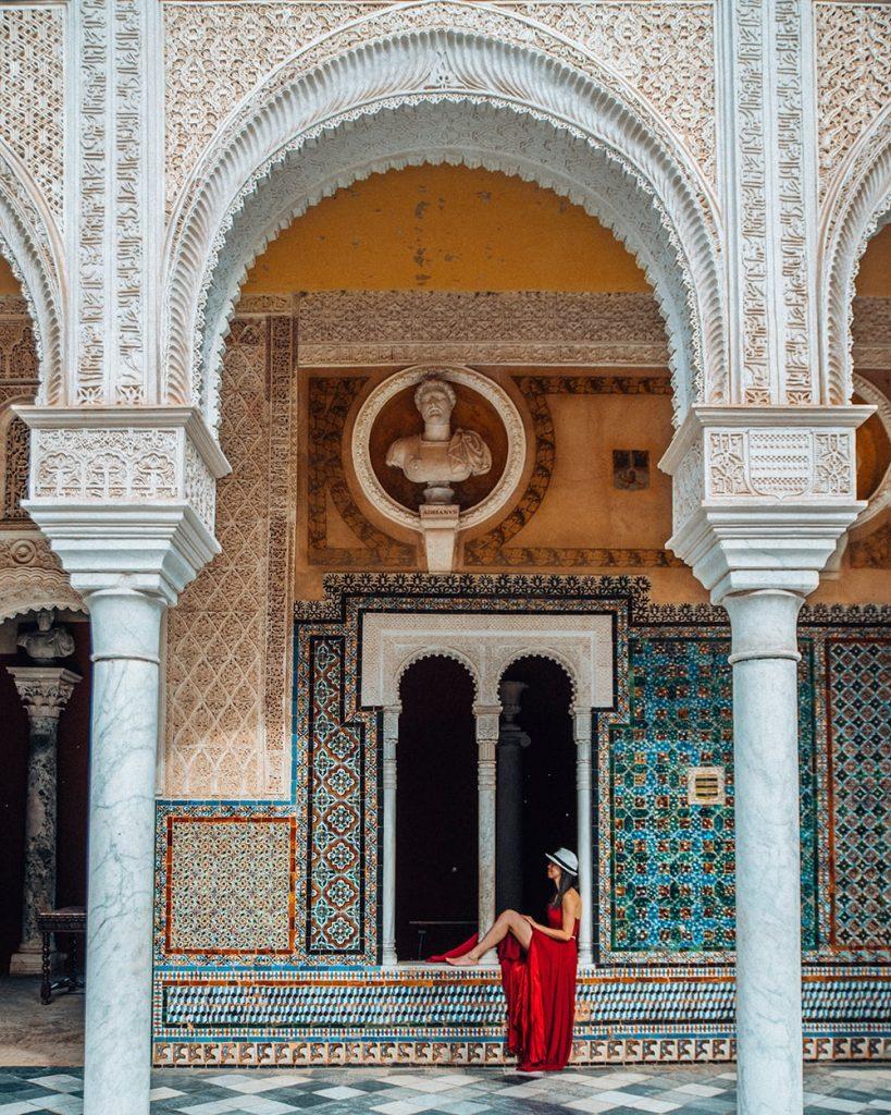 girl sitting in casa de pilatos in seville spain