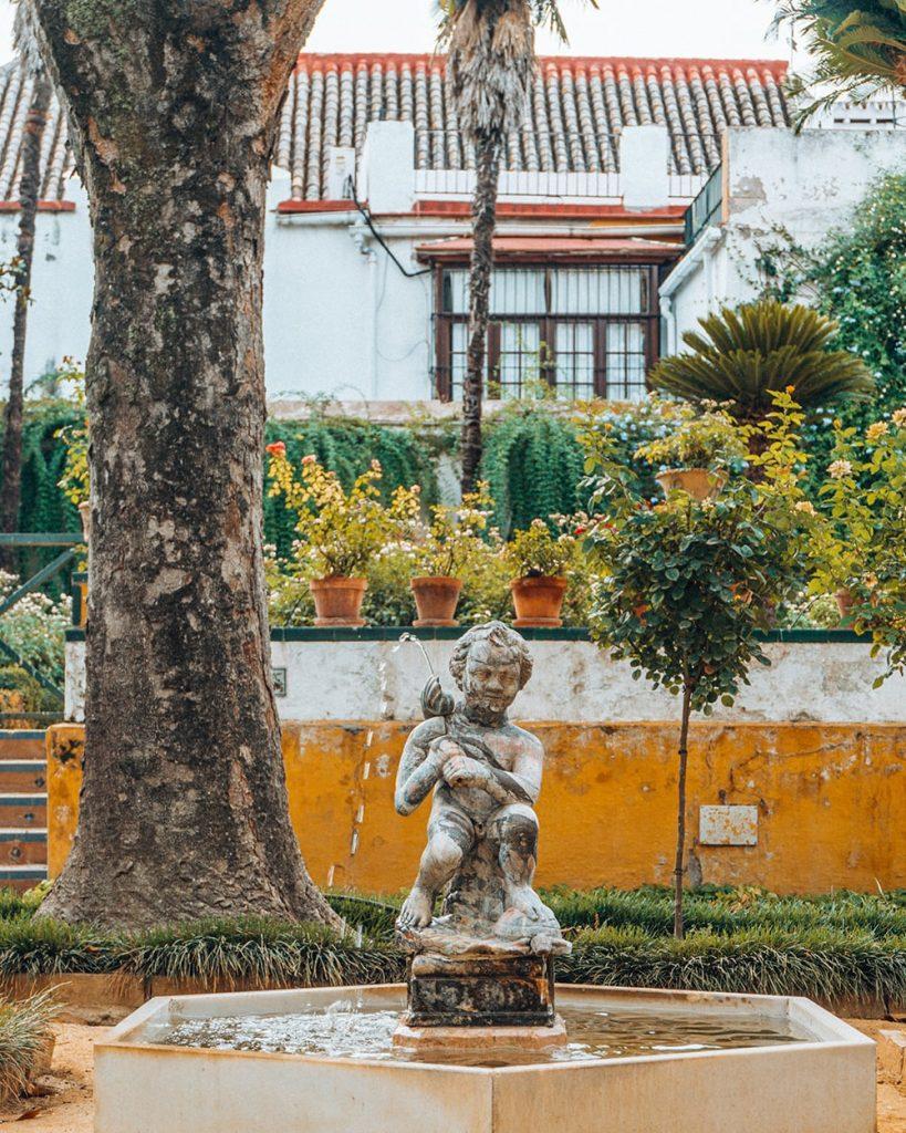 a statue in the patio of casa de pilatos in seville spain