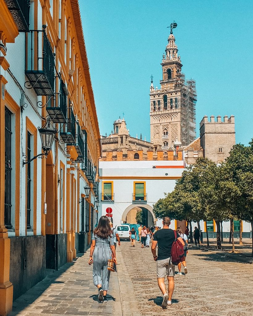 tourists walking towards the giralda tower in seville spain