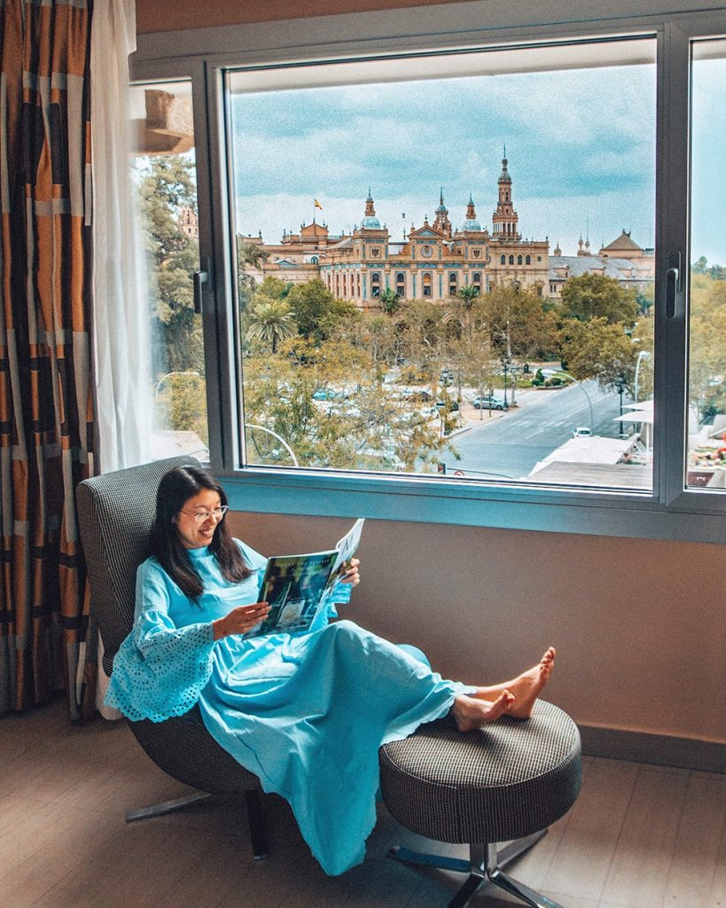 girl sitting in a hotel room in seville spain with a beautiful view out the window