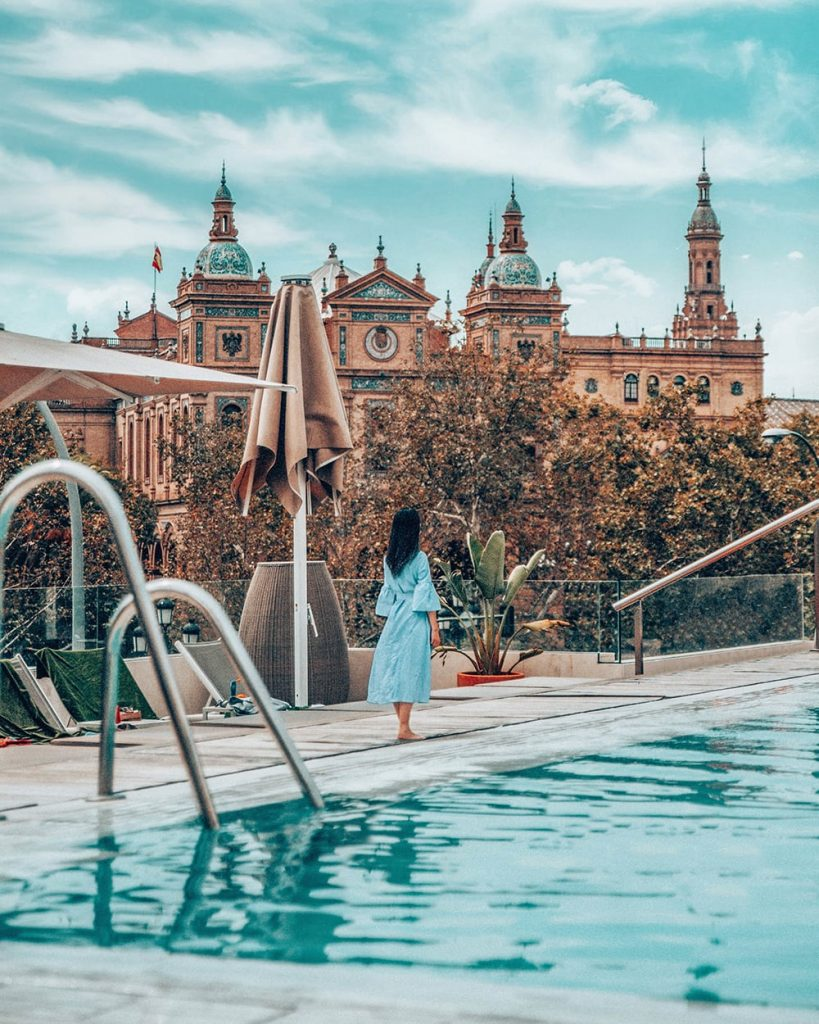 girl standing by a pool in a hotel in seville spain