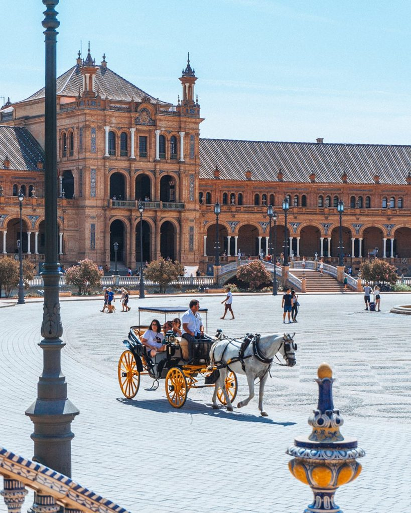 a horse carriage in the middle of an empty plaza de espana in sevilla spain