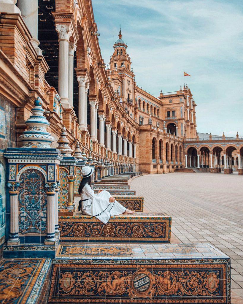 girl sitting on the tiled alcoves of plaza de espana in seville spain