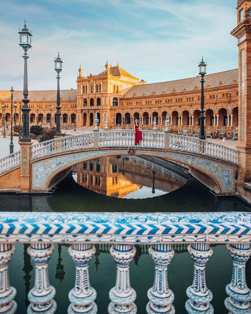 a girl sitting on a bridge in front of water reflections in a square in seville