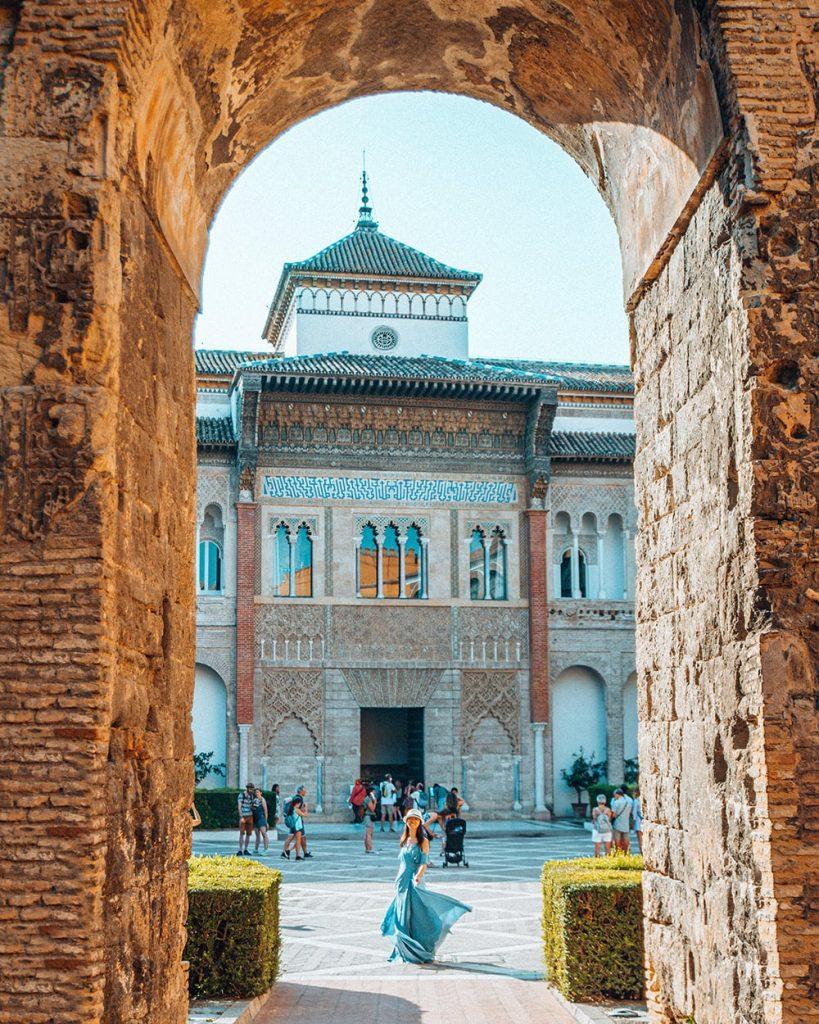girl standing amongst the moorish architecture of royal alcazar of seville spain