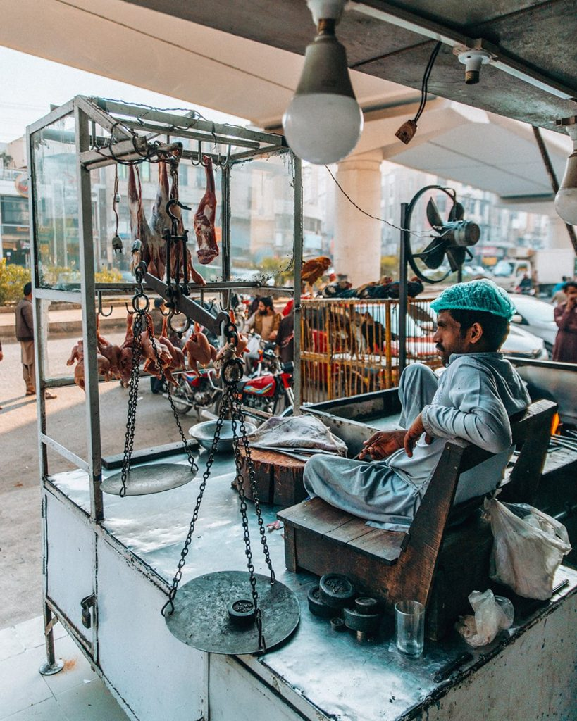 a man sitting outside a restaurant in lahore pakistan