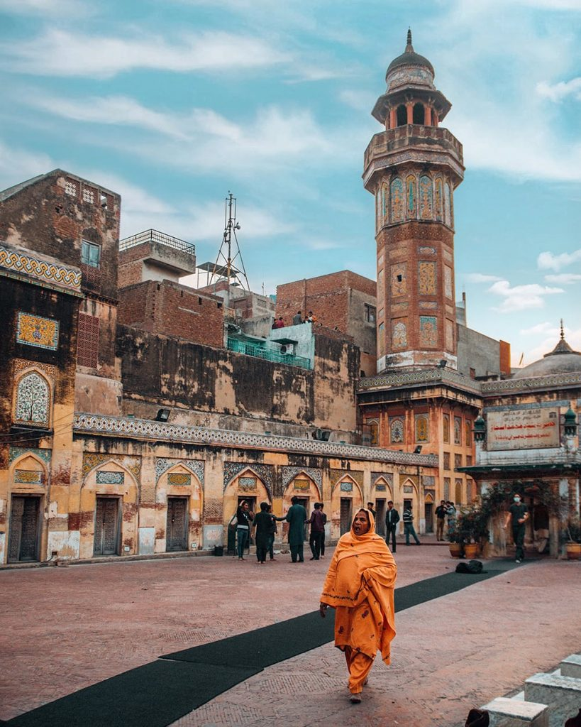 a woman walking inside masjid wazir khan in lahore pakistan