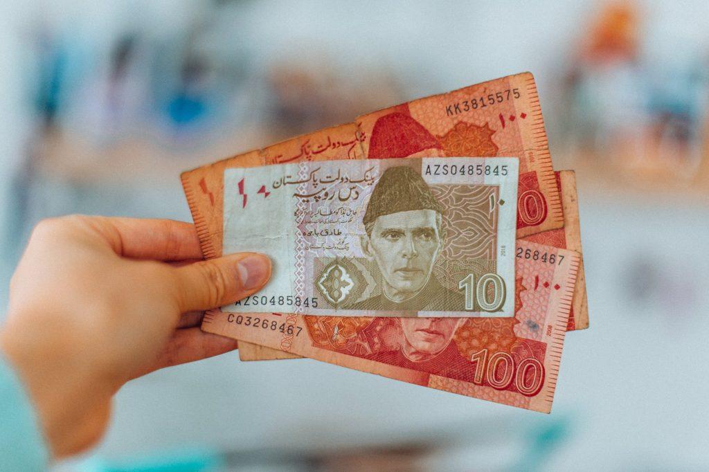 hand holding pakistani rupee bills