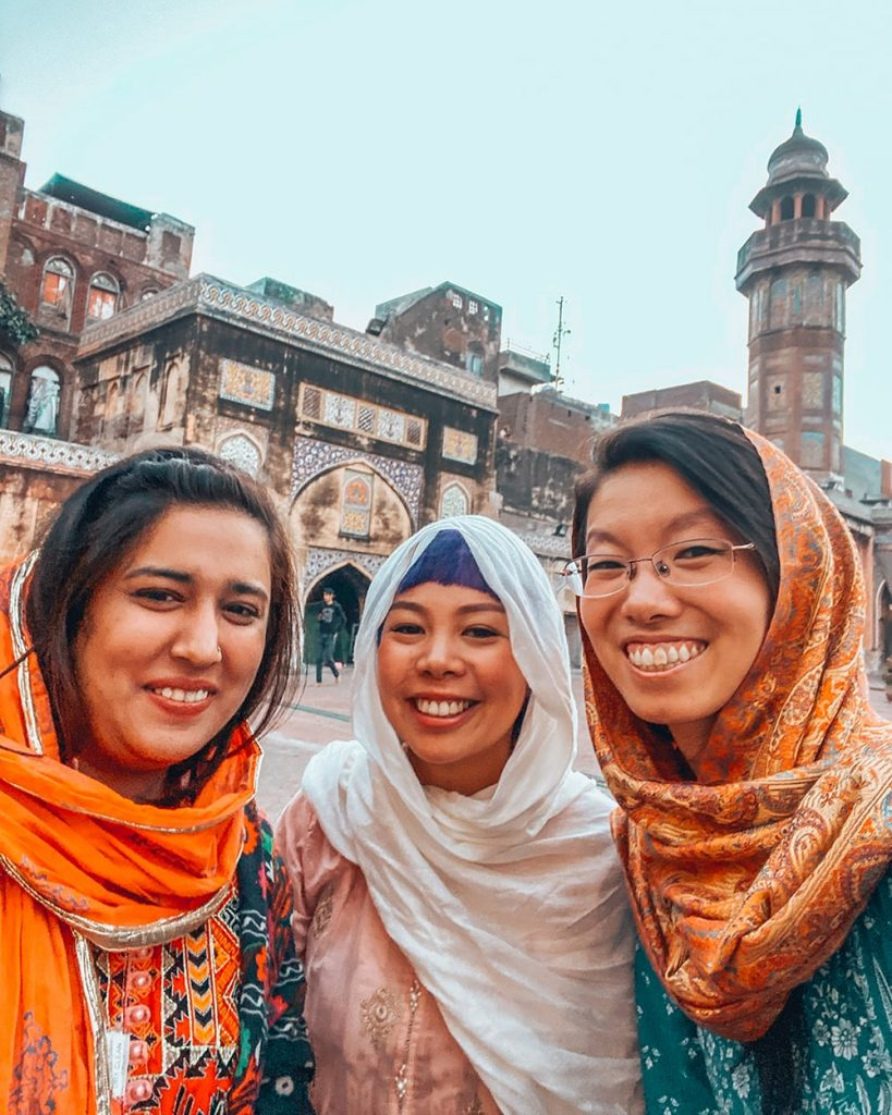 a local woman in lahore pakistan taking a selfie with two tourists