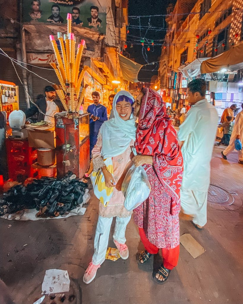 a tourist posing with a local in lahore night market