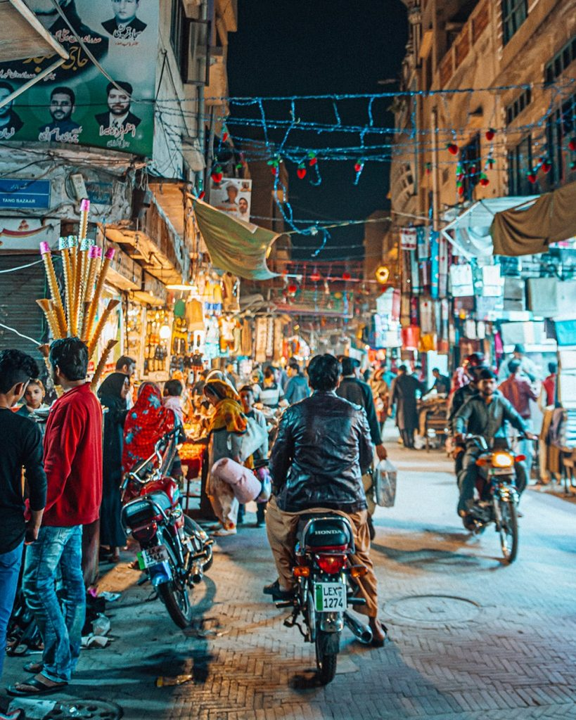man riding a motorbike in a night market in lahore pakistan