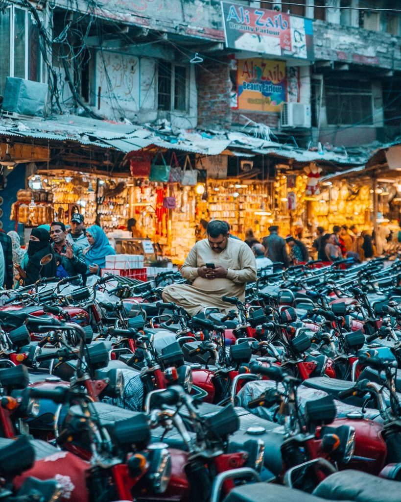 a man staring at his phone amidst a sea of bikes in lahore pakistan