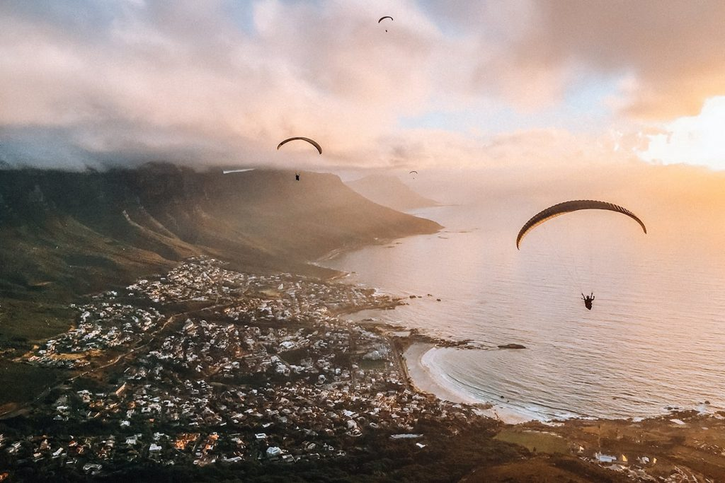 a parachute flying above the coastline of cape town south africa