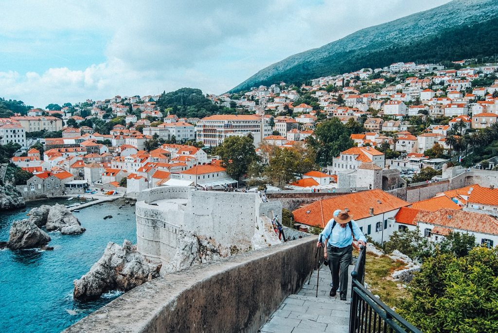 man walking by houses with red roofs in dubrovnik croatia