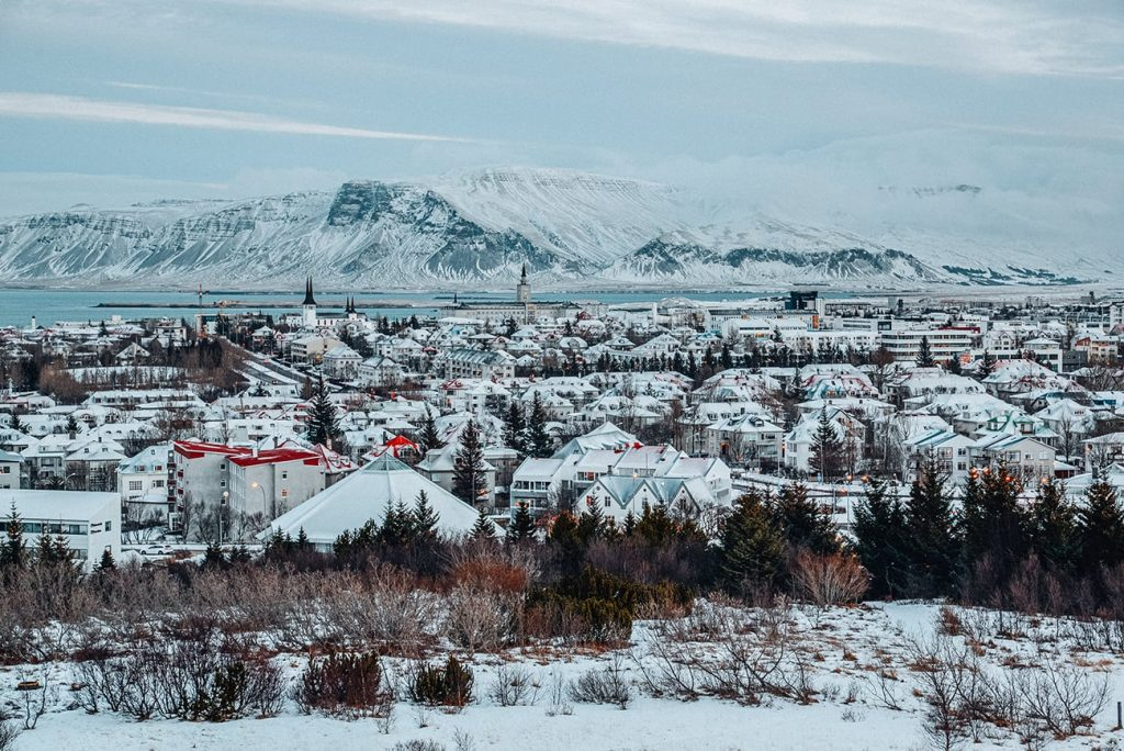 the view of Reykjavík iceland with all its houses and snowcapped moutains