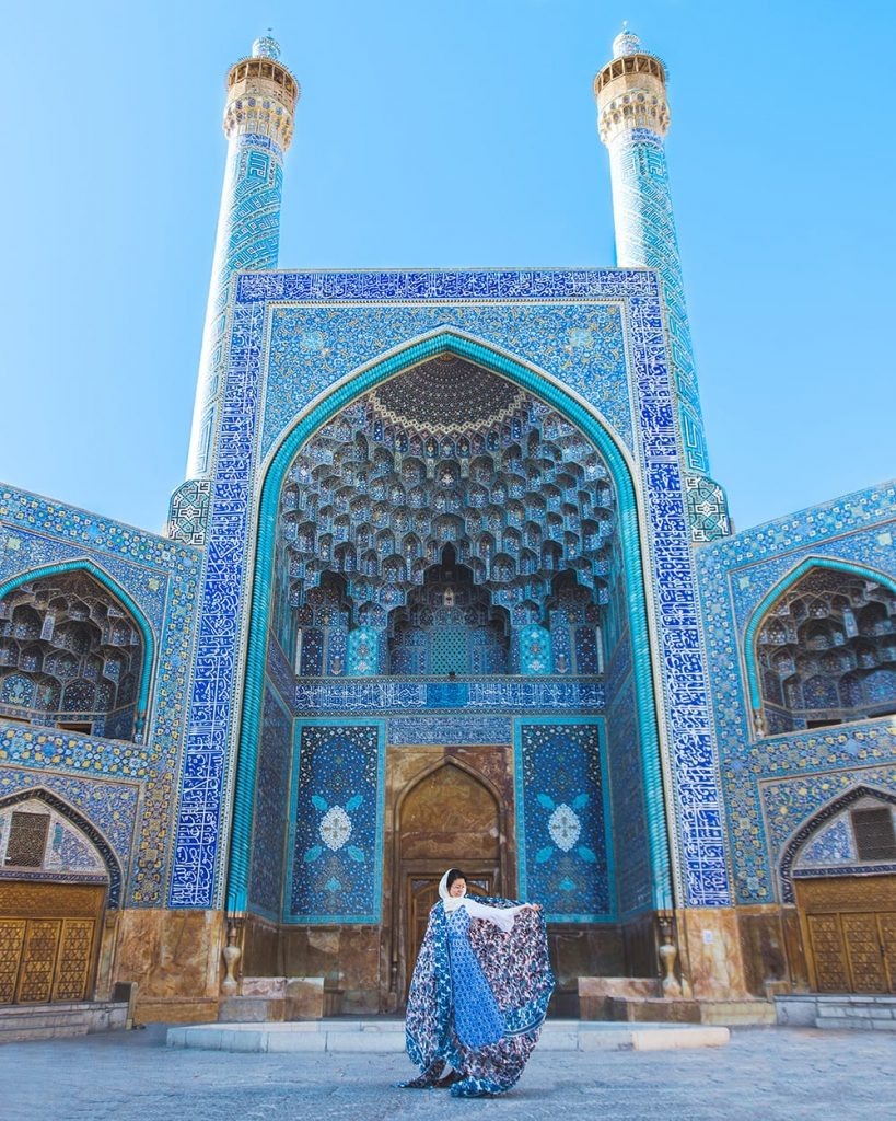 girl standing in front of shah mosque in esfahan iran