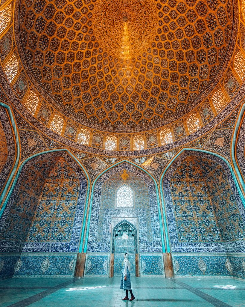 girl walking inside sheikh lotfollah mosque in esfahan iran