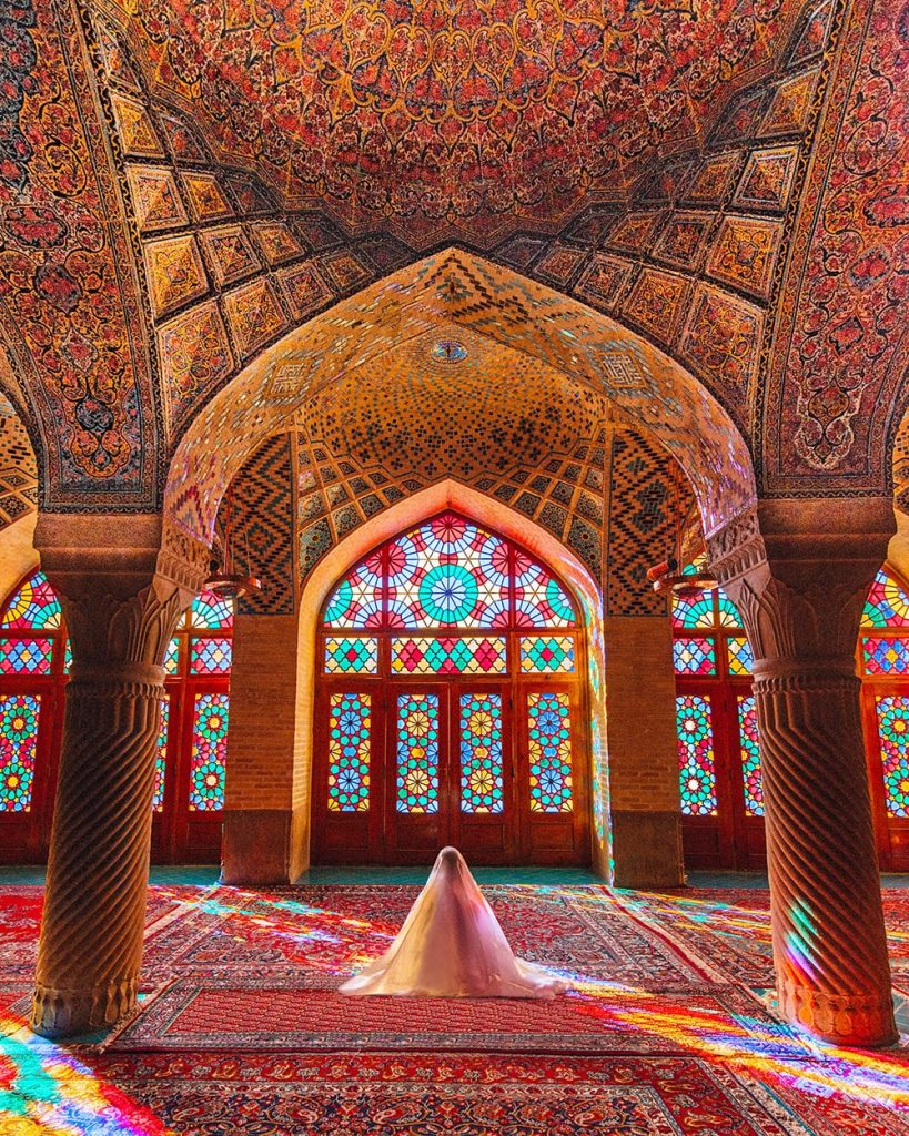 girl sitting in the pink mosque in shiraz iran