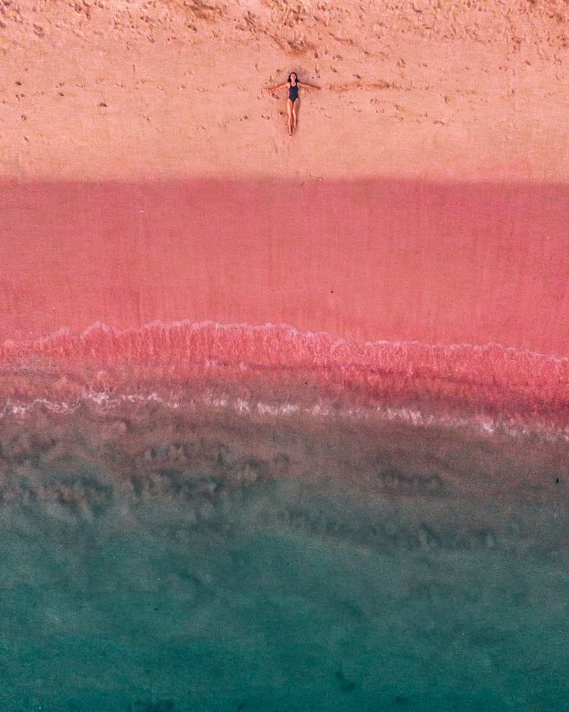 girl lying on the pink beach in komodo island indonesia