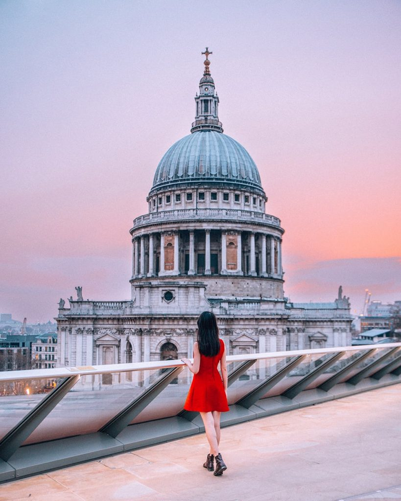 girl standing on a terrace with a view of st pauls cathedral in front of her in london