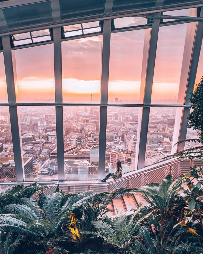 a girl sitting near the windows in sky garden london with a view of the city beneath her