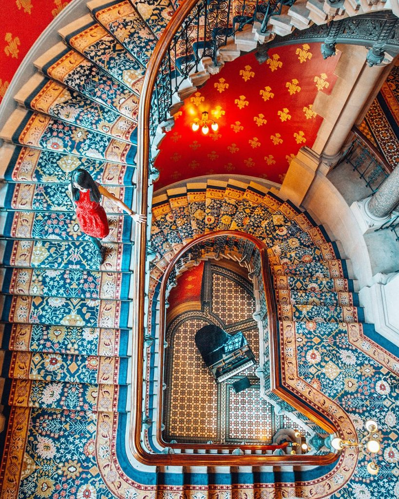 a girl walking down the stairs of st pancras renaissance hotel in london