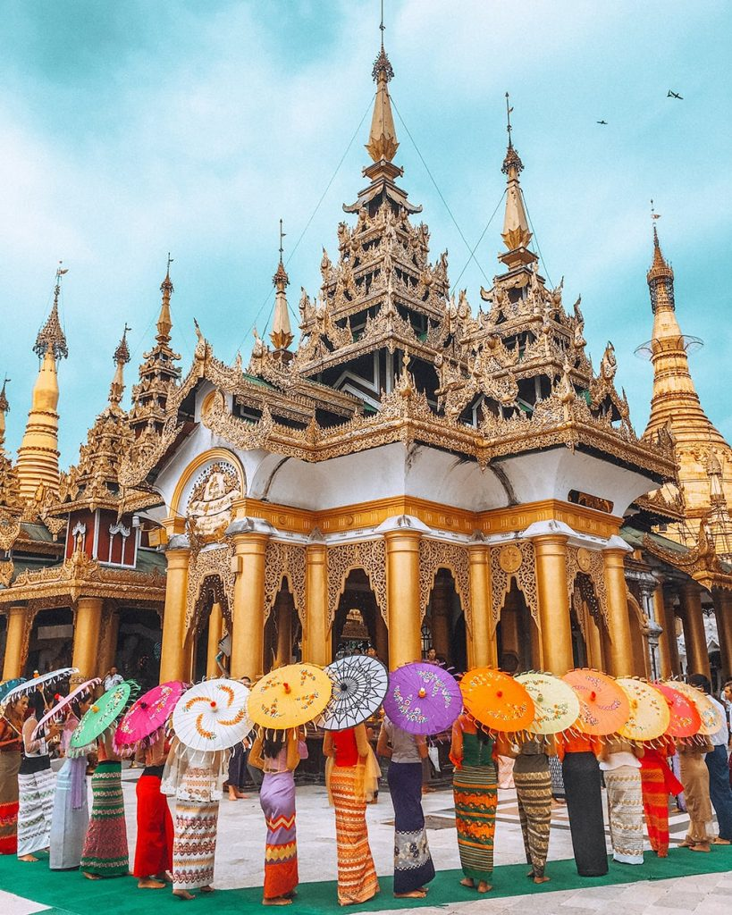 women posing with colorful umbrellas in shwedagon pagoda in yangon myanmar