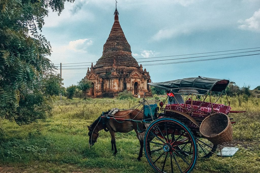 a horse carriage in front of an ancient temple in bagan myanmar