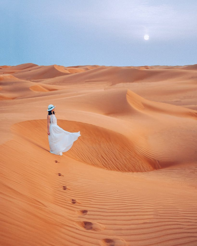 girl standing on a desert with a white dress in oman