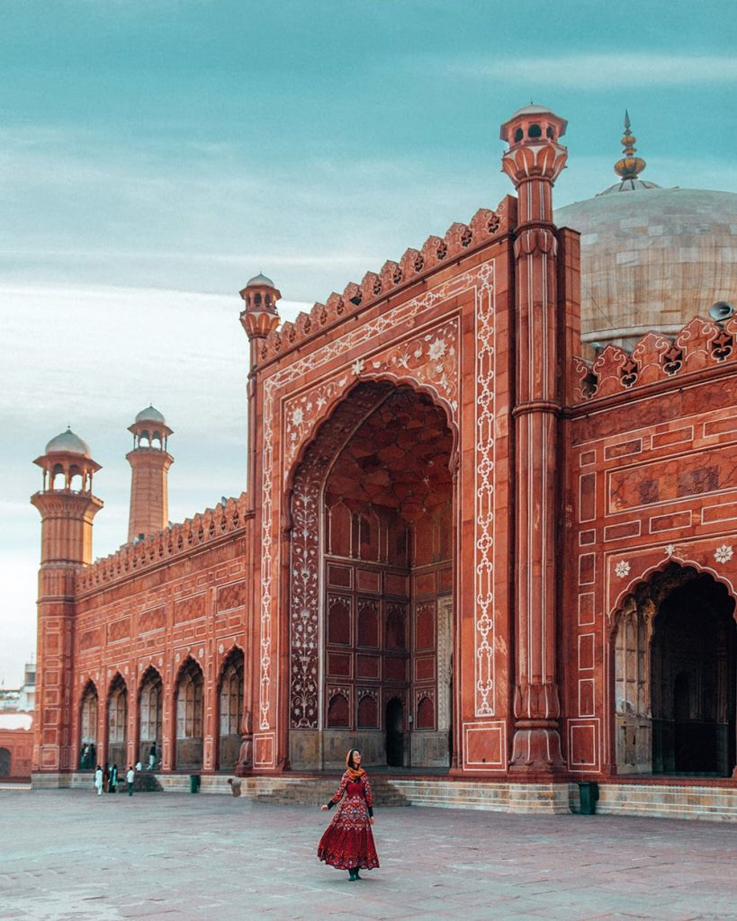 a girl standing in front of badshahi mosque in lahore pakistan