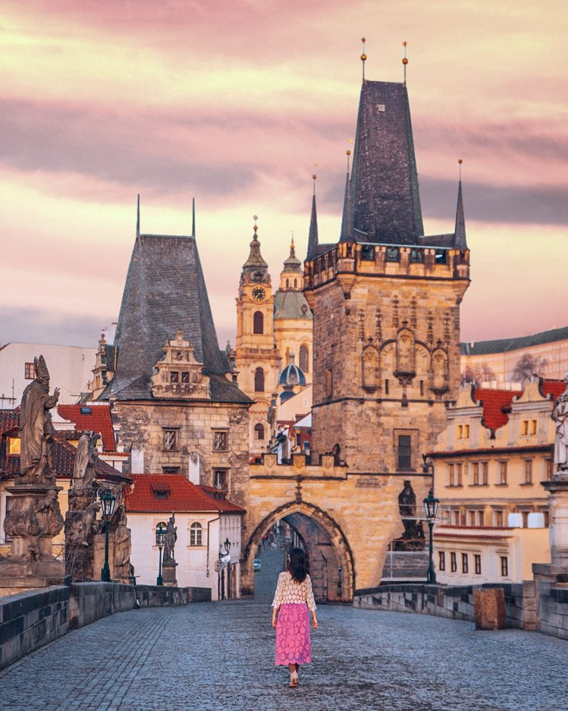 girl walking towards a castle in the old town of prague czech republic