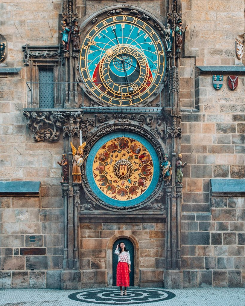a girl standing in front of the astronomical clock in the old town of prague czech republic